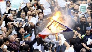 Demonstrators burn the French national flag after Friday prayers in Algiers