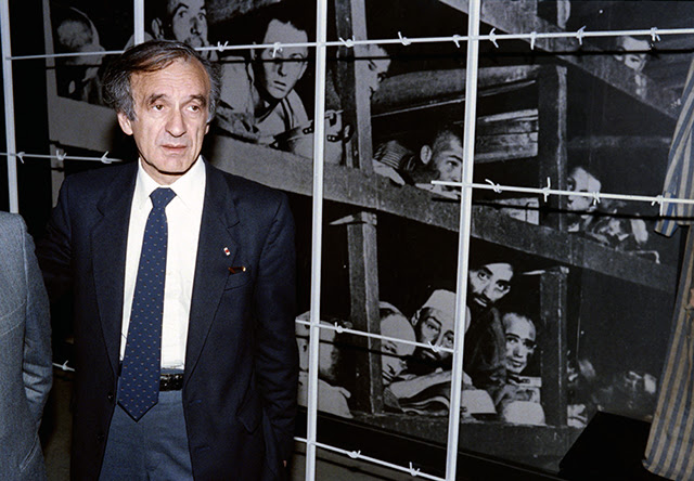 """1986 Nobel Peace prize winner and writer Elie Wiesel (L) stands in front of a photo of himself (bottom right hand corner) and other inmates, taken at the Buchenwald concentration camp in 1945, during his visit on December 18, 1986 to the Holocaust Memorial Center """"Yad Vashem"""" in Jerusalem. Wiesel, a naturalized American citizen, was born 30 September 1928 in Sighet (Romania). A survivor of the Nazi concentrations camp, he has spent his adult life fighting for the rights of Holocaust victims. AFP PHOTO SVEN NACKSTRAND / AFP PHOTO / SVEN NACKSTRAND"""