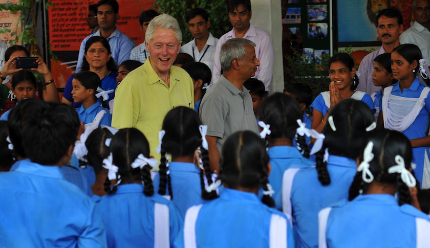 Former US president Bill Clinton (C) smiles as he speaks with Indian schoolchildren during a visit in Sanganer on July 16, 2014. Clinton is on a five-country tour through Asia, visiting projects that work in conjunction with the Clinton Foundation. AFP PHOTO / STR (Photo credit should read STRDEL/AFP/Getty Images)