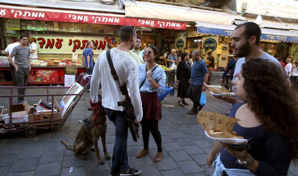 "Young Israelis (mostly soldiers on weekend vacation) carry their personal rifles at the Jerusalem outdoors Mahne Yehuda market on October 9, 2015. The mayor of Jerusalem, Nir Barkat, has gone as far as to encourage residents who own guns to carry them around with them ""Possessing weapons increases the confidence of residents,"" he said as he toured occupied and annexed east Jerusalem, with his own gun in full sight. AFP PHOTO / GALI TIBBON / AFP PHOTO / GALI TIBBON"